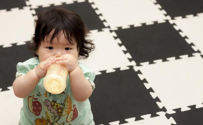 クッションマットの上でおすわりする赤ちゃんのイメージ