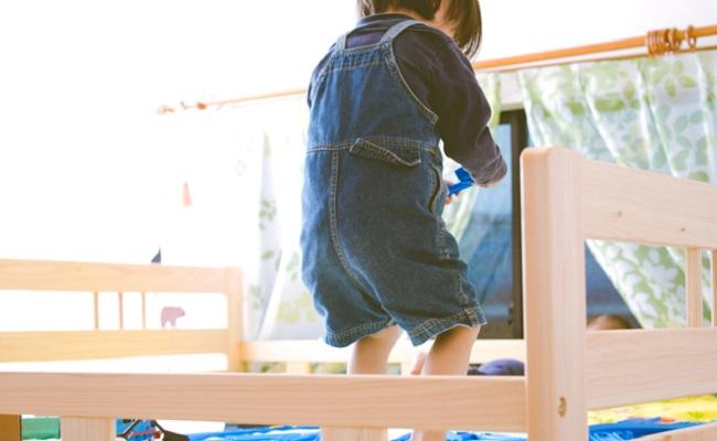 子供がベッドで遊んでいるイメージ