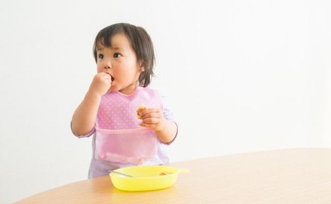 食事エプロンをして食事している赤ちゃん