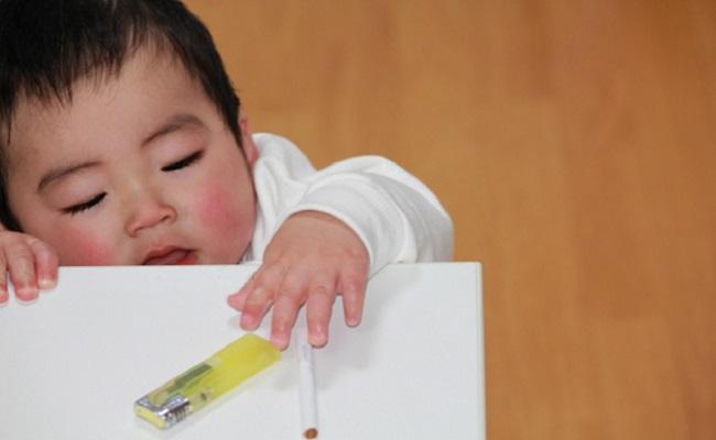 タバコに手を伸ばす赤ちゃんのイメージ