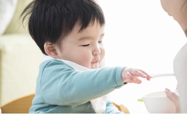 食事に手を伸ばす赤ちゃんのイメージ