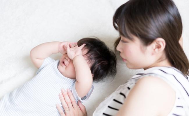 寝ぐずりしている赤ちゃんと寝かしつけているママのイメージ