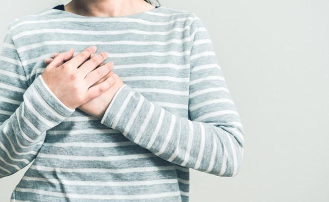 胸の痛みを訴える女性のイメージ