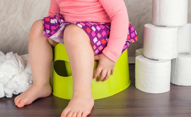 トイレトレーニング中でおまるに座っている子どものイメージ
