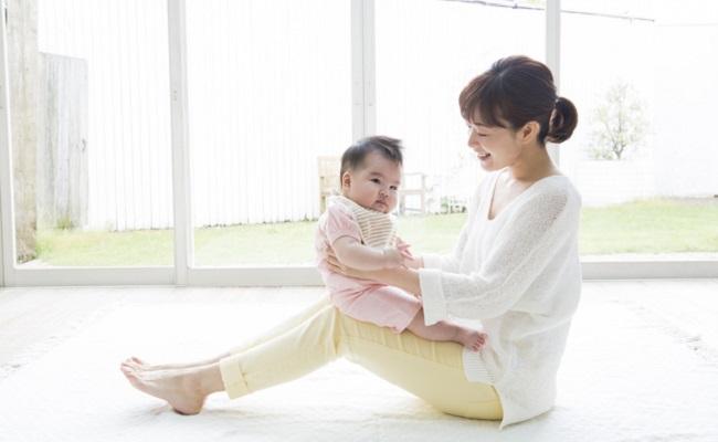 ママの足の上で遊ぶ赤ちゃん