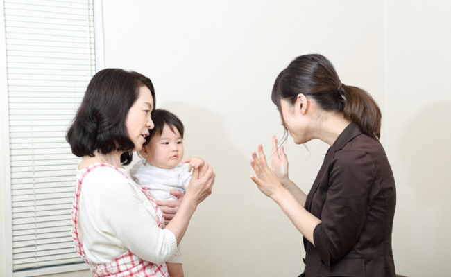 保育士さんに赤ちゃんを預けるママ