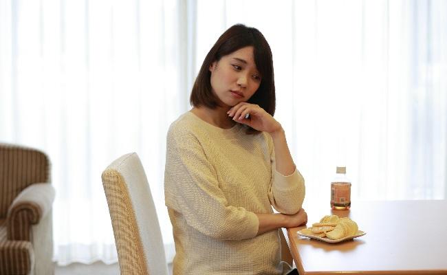 スナック菓子を食べるか悩む妊婦さん