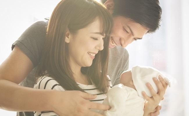 新生児を見守る夫婦のイメージ