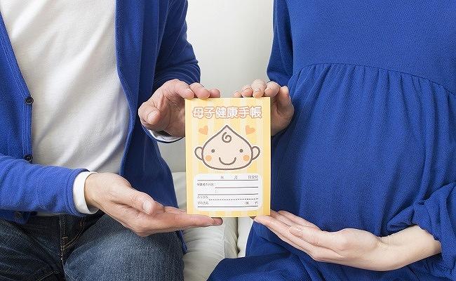 母子手帳を持つ夫婦のイメージ