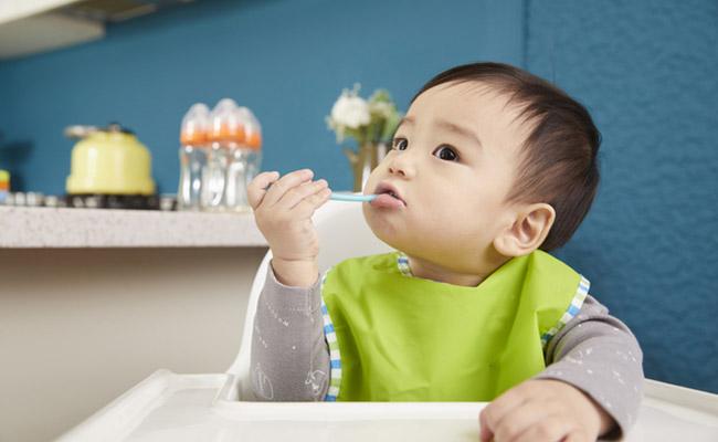 スプーンを使う赤ちゃんのイメージ