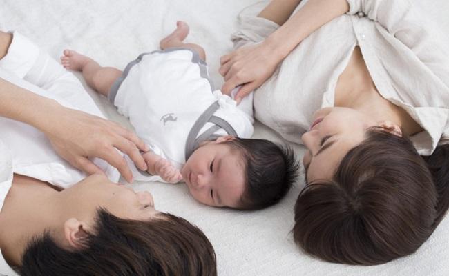 添い寝しているパパママと赤ちゃんのイメージ