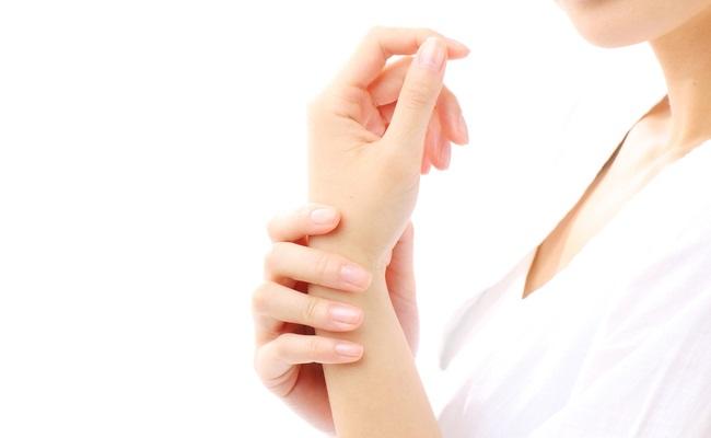 手首を触る女性