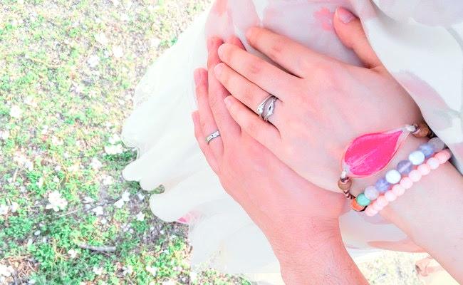 おなかの上に置いた夫婦の手