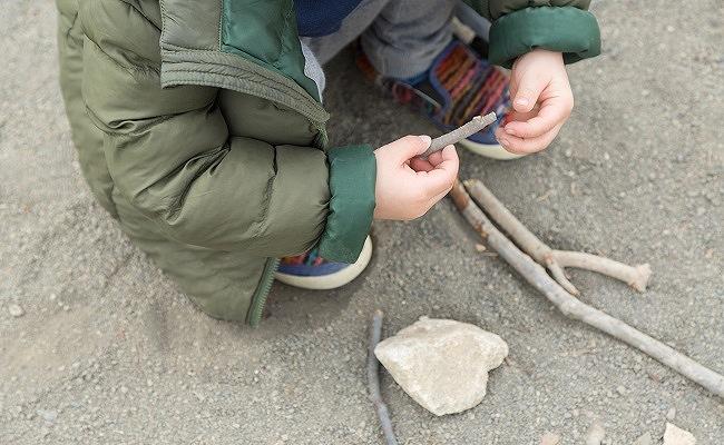 木や石を拾う幼児