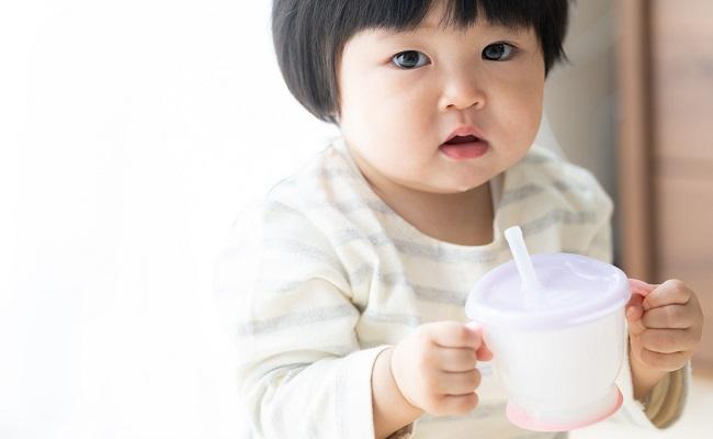 ストローマグを使って飲む赤ちゃん
