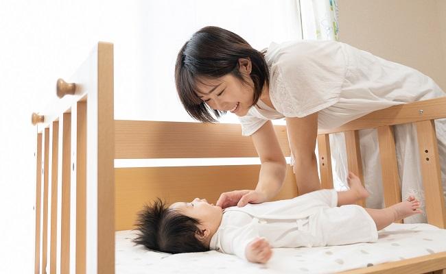 ベビーベッドで赤ちゃんをあやすママ