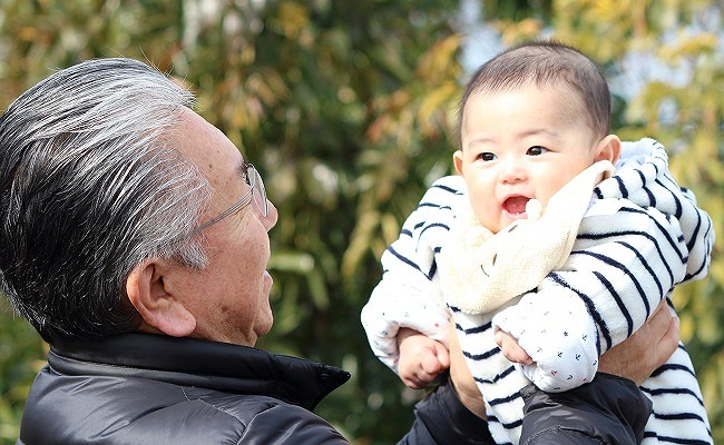 赤ちゃんを高い高いしている祖父