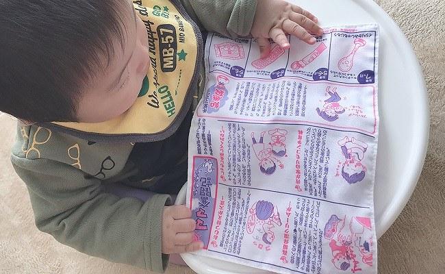 赤ちゃん新聞で遊ぶ赤ちゃん