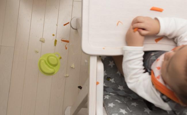 赤ちゃんが手づかみ食べをして離乳食をこぼしたイメージ
