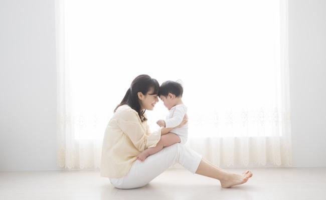 室内で遊ぶ赤ちゃんと母親のイメージ