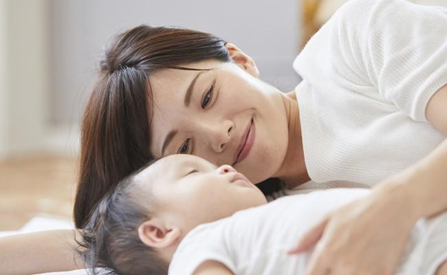 お昼寝中の赤ちゃんと見守るママ