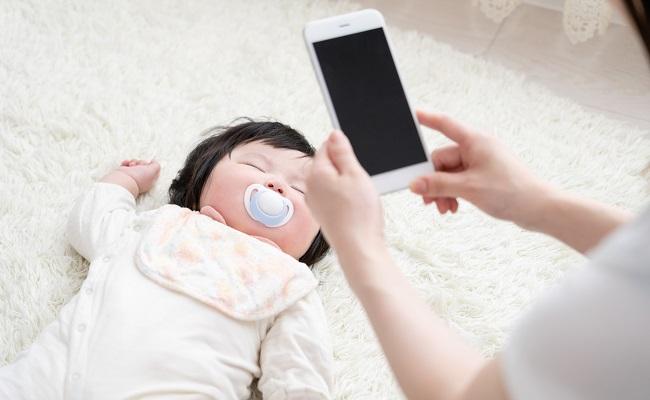 赤ちゃんを撮影するママ