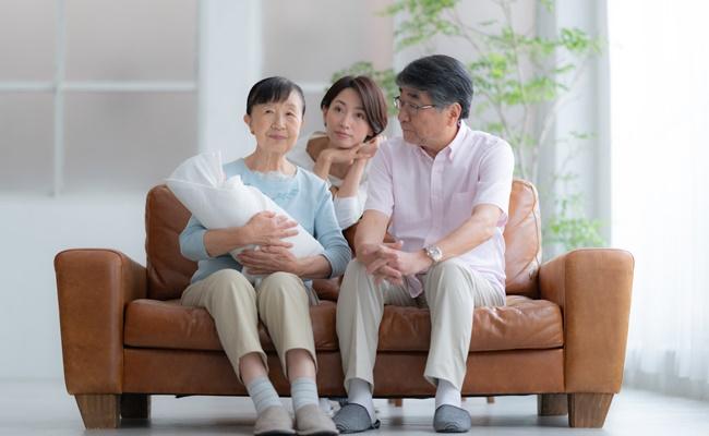 赤ちゃんを抱く両親と不満そうなママ