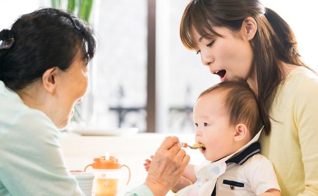 離乳食をあげるおばあちゃんとお母さん
