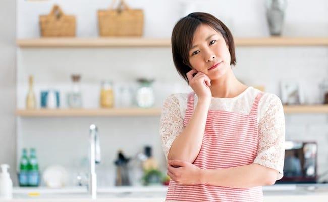 キッチンで悩んでいる女性のイメージ