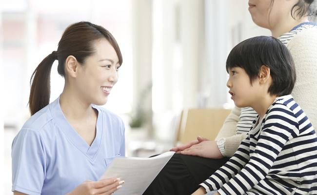 看護師さんとお話しする子供とお母さん