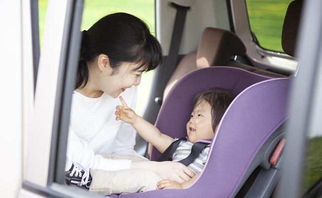 チャイルドシートに座っている子供とお母さん