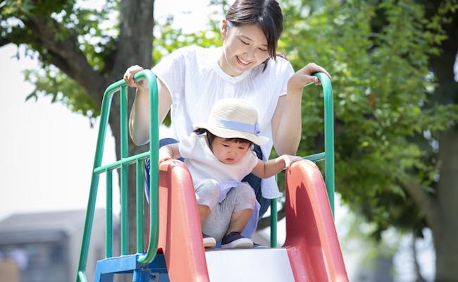 滑り台で遊ぶ親子のイメージ