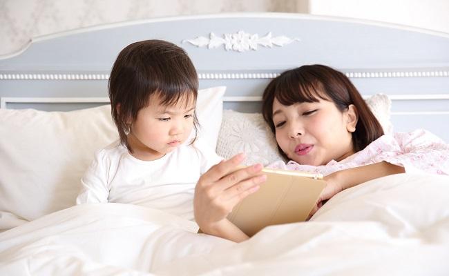 ベッドで絵本を読む親子