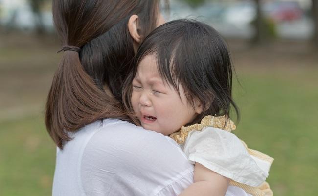 泣いている赤ちゃんを抱くママ